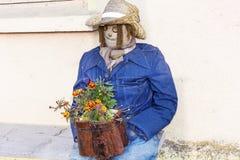 与花的装饰坐的稻草人 免版税库存照片