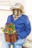 与花的装饰坐的稻草人 库存照片