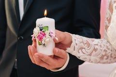 与花的装饰的白色蜡烛在新婚佳偶的手上 家庭壁炉边的概念 库存图片