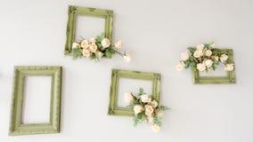 与花的绿色木制框架在墙壁上 免版税库存图片