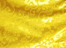 与花纹花样的金黄丝绸 库存图片