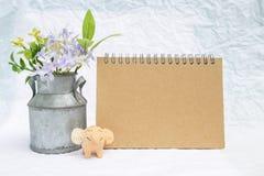 与花罐子花瓶和微笑的大象黏土的空白的棕色卡片在白色纹理背景 免版税库存照片