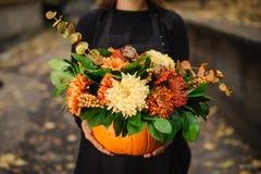 与花美丽的花束的橙色南瓜在妇女手上 库存照片