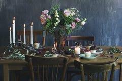 与花花束、蜡烛和dess的欢乐桌设置 免版税库存图片