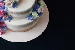 与花装饰的蛋糕在黑桌上 拷贝空间 库存照片