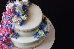 与花装饰的蛋糕在黑桌上 拷贝空间 免版税库存图片