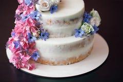 与花装饰的蛋糕在黑桌上 库存图片