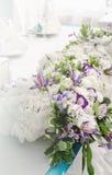 与花豪华的叶子的富有的装饰,白色八仙花属,奶油色玫瑰,紫色南北美洲香草的豪华宴会桌,蓝色 图库摄影