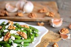 与芳香抚人的选矿的健康青豆沙拉 温暖青豆沙拉用酸奶干酪、核桃、大蒜和香料 图库摄影
