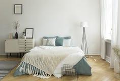 与苍白灰绿色和白色亚麻布、枕头和毯子的一张大舒适的床在与窗口的妇女` s明亮的卧室内部 免版税库存照片