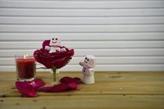 与英国兰开斯特家族族徽的浪漫冬天季节摄影图象和与蛋白软糖愉快的雪人的一个被点燃的蜡烛在桌上的花里面 免版税库存图片