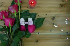 与英国兰开斯特家族族徽的浪漫冬天季节摄影图象和与蛋白软糖睡觉的雪人的一个被点燃的蜡烛在桌上的瓣的 免版税库存图片