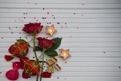 与英国兰开斯特家族族徽的浪漫颜色圣诞节摄影图象点燃了蜡烛和豪华巧克力与红色和绿色中看不中用的物品装饰 免版税库存照片
