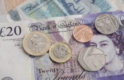 与英镑钞票的新的1英镑硬币 库存照片