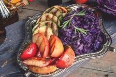 与苹果和葱烤大块的被炖的红叶卷心菜,晒干用柠檬和橄榄油在一个美丽的盘 免版税库存照片