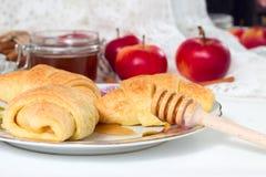 与苹果种子和蜂蜜的新近地被烘烤的自创甜小圆面包在茶碟的白色桌上 库存照片