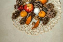 与苹果计算机、蜜桔、坚果、杏仁、圣诞节球和杉木锥体的被绣的餐巾在胶合板 库存图片