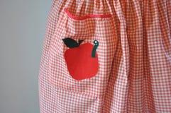 与苹果计算机和蠕虫补花的红色和白色方格花布围裙 免版税库存照片