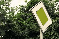 与茂盛植物的超现实的绿色交通标志概念-社交发布与拷贝空间的概念 优先权标志特写镜头  免版税库存照片