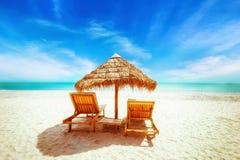与茅草屋顶伞的热带放松的海滩和椅子 免版税图库摄影