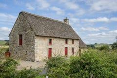 与茅草屋顶屋顶的英国石村庄 免版税库存图片