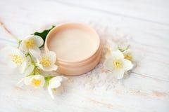 与茉莉花开花、罐秀丽奶油和海盐的温泉设置在白色木桌上 免版税库存图片