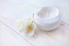 与茉莉花开花的面霜在白色木桌上 库存照片