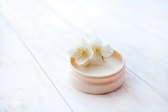 与茉莉花的润湿的面霜在白色木桌上开花 关闭 免版税图库摄影