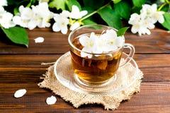 与茉莉花的芬芳茶在一张木桌上的一个玻璃杯子 免版税库存图片