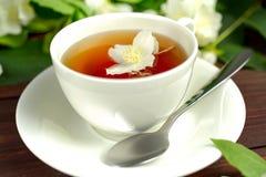 与茉莉花的茶在一张木桌上的一个白色杯子 免版税库存图片