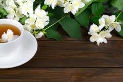 与茉莉花的茶在一张木桌上的一个白色杯子 免版税图库摄影