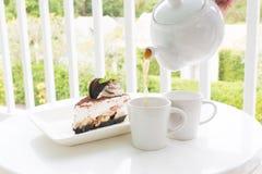 与茶具的巧克力蛋糕在庭院里 免版税库存图片