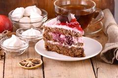 与茶杯和蛋白甜饼的巧克力蛋糕 免版税库存图片