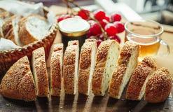 与茶杯和frui的新整个五谷面包或黑麦面包切片 库存照片
