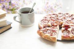 与茶杯子、书和花的整个李子蛋糕在木backgr 免版税图库摄影