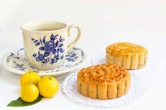 与茶杯的传统月饼和在叶子的小三个桔子 免版税图库摄影