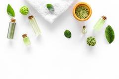 与茶橄榄油的有机化妆用品集合和在瓶白色桌背景舱内甲板的海盐放置大模型 免版税图库摄影