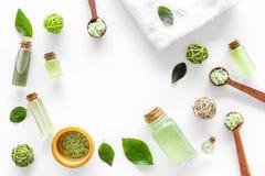 与茶橄榄油的有机化妆用品集合和在瓶白色桌背景舱内甲板的海盐放置框架大模型 免版税库存图片