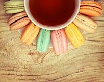 与茶的五颜六色的法语Macarons在木背景的 库存图片