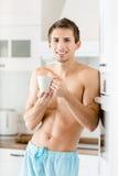 与茶的半裸体的年轻男性在厨房的 免版税库存照片