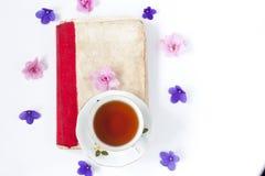 与茶的浪漫背景淡紫色花和减速火箭的书在白色桌 免版税库存照片