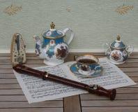 与茶碟的英国茶杯、茶壶和糖罐、节拍器音乐的和一支块长笛在音乐板料  免版税库存照片