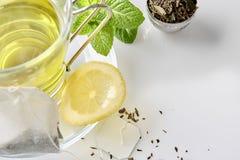 与茶袋特写镜头的绿茶用薄菏和柠檬冠上 免版税图库摄影