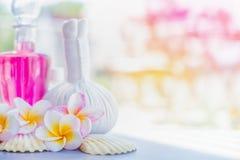 与草本压缩邮票、桃红色化妆水瓶和壳的黄色赤素馨花花在夏天自然背景 温泉或wellnes 免版税库存图片
