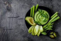 与草本hummus或pesto垂度的绿色菜快餐板 健康未加工的夏天开胃菜盛肉盘 免版税库存照片