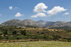 与草甸、山和蓝天的希腊风景 免版税库存图片