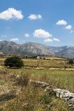 与草甸、山和蓝天,白色教堂的希腊风景 免版税库存照片