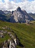 与草甸、瑞士山中的牧人小屋、峰顶和供徒步旅行的小道的白云岩山 免版税图库摄影