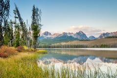 与草的山反射在爱达荷 库存图片