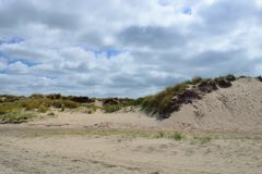 与草的沙丘在De Koog特塞尔海滩在有多云天空的荷兰 图库摄影